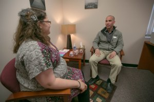 Amberkay Crotts (left), a student employee, and  Napoleon Andriopoulos, Ph.D., psychology resident and UND staff psychologist, discuss issues related to student stress in the UND Counseling Center inside McCannel Hall.